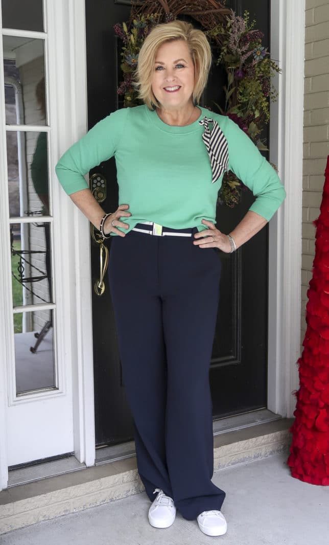 Fashion Blogger 50 Is Not Old wearing a Jade sweater with a striped scarf with navy wide leg pants.