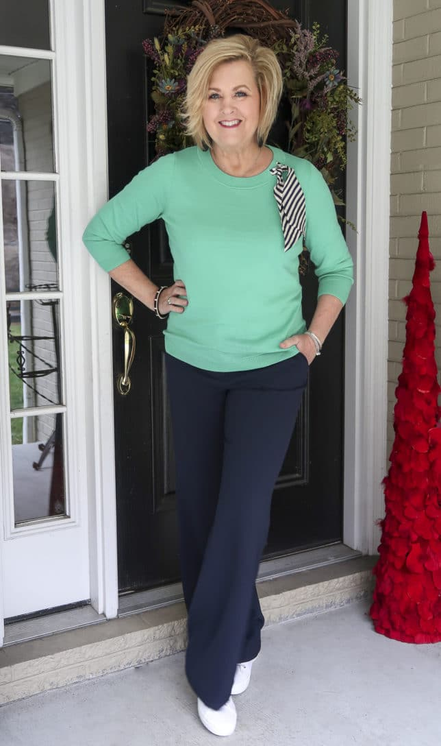 Fashion Blogger 50 Is Not Old wearing a light Jade sweater with a striped scarf with navy wide leg pants and sneakers