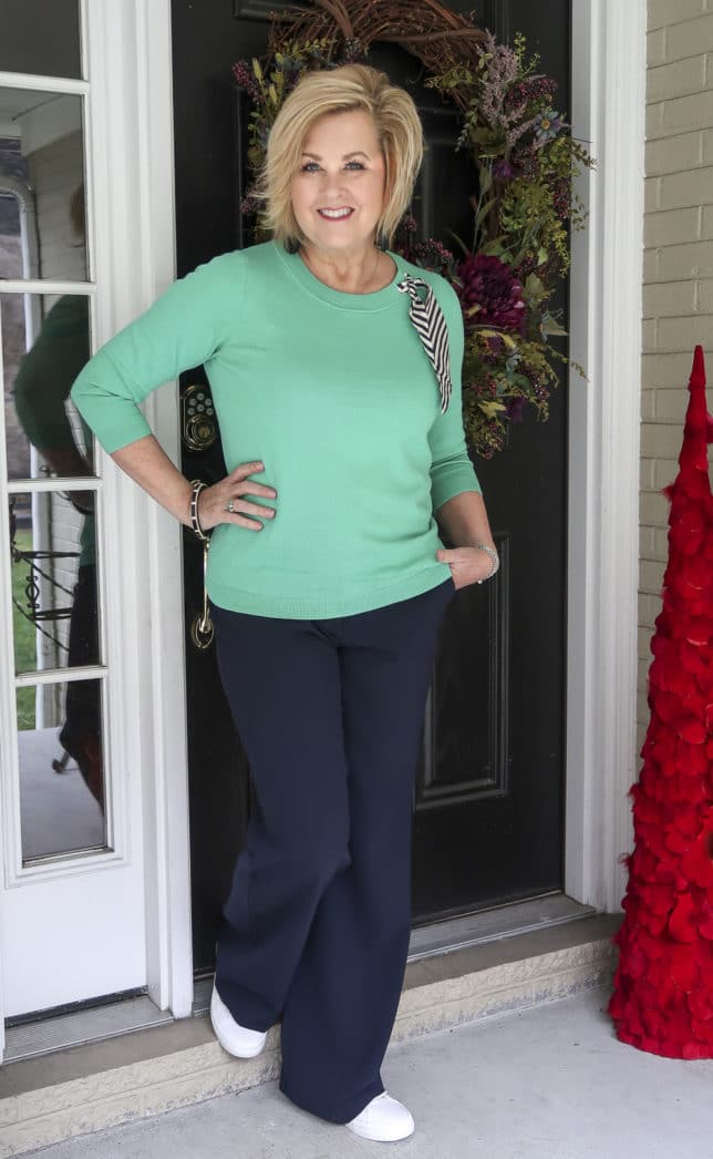 Fashion Blogger 50 Is Not Old wearing a light Jade sweater with a striped silk scarf with navy wide leg pants.