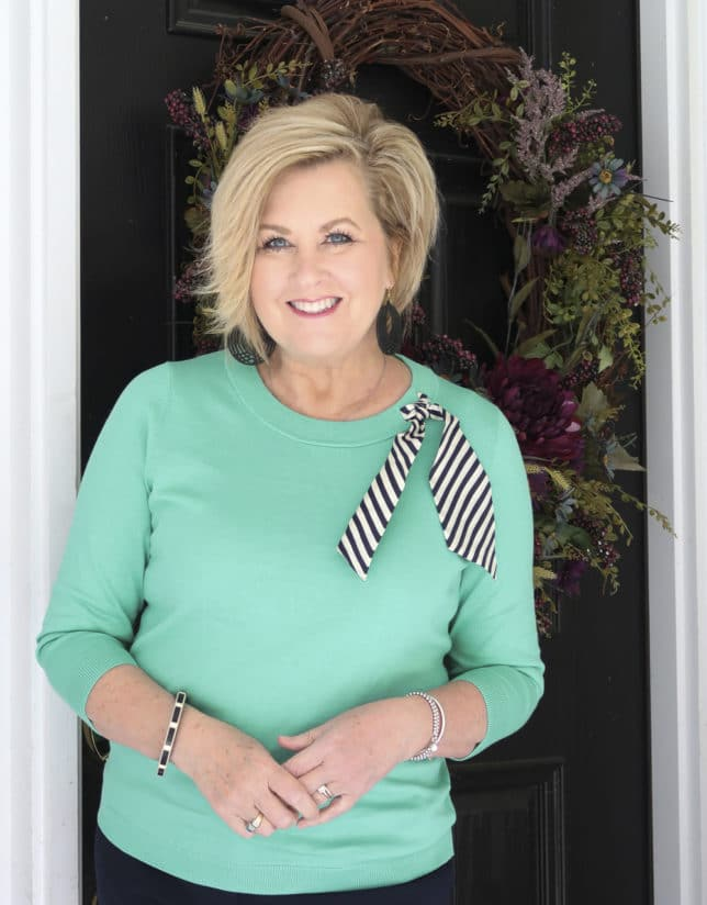 Fashion Blogger 50 Is Not Old wearing a light Jade sweater with a striped silk scarf