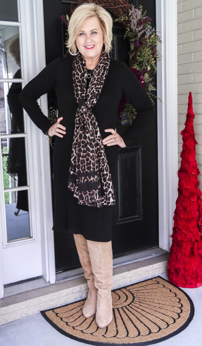 Fashion blogger 50 Is Not Old shows us how a classic black sweater dress looks updated with the addition of the leopard print scarf and knee boots.