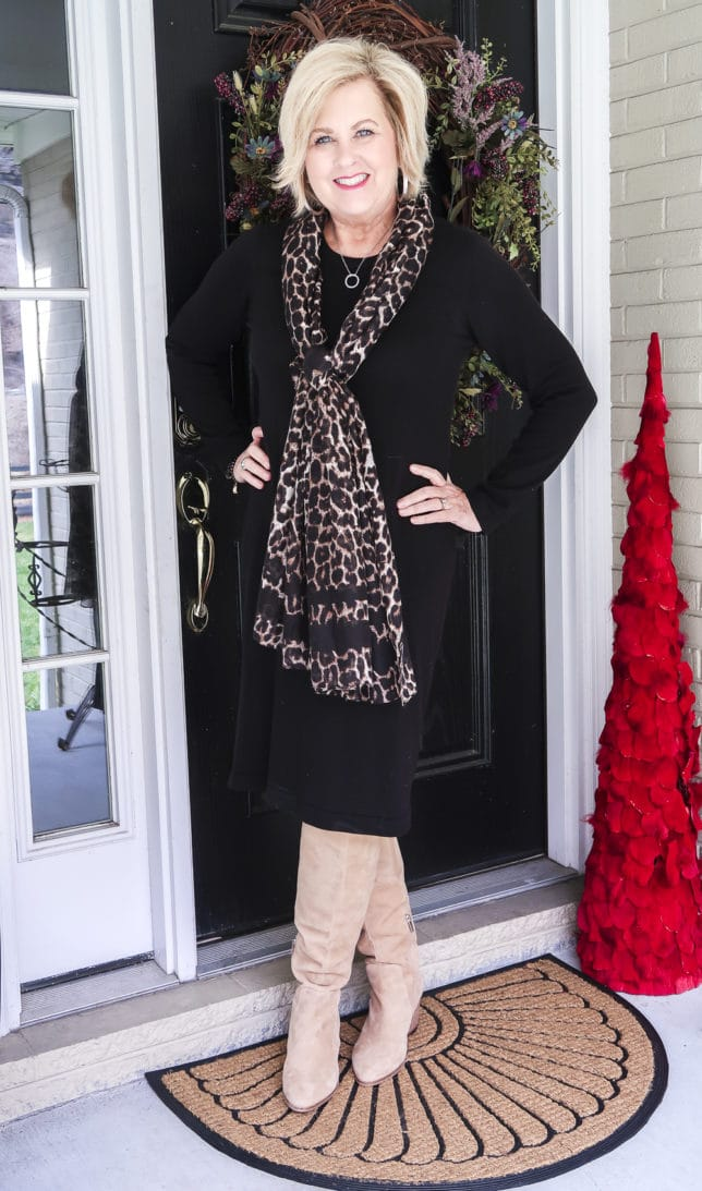 Fashion blogger 50 Is Not Old shows us how a classic black dress looks updated with the addition of the leopard print scarf and suede knee boots.