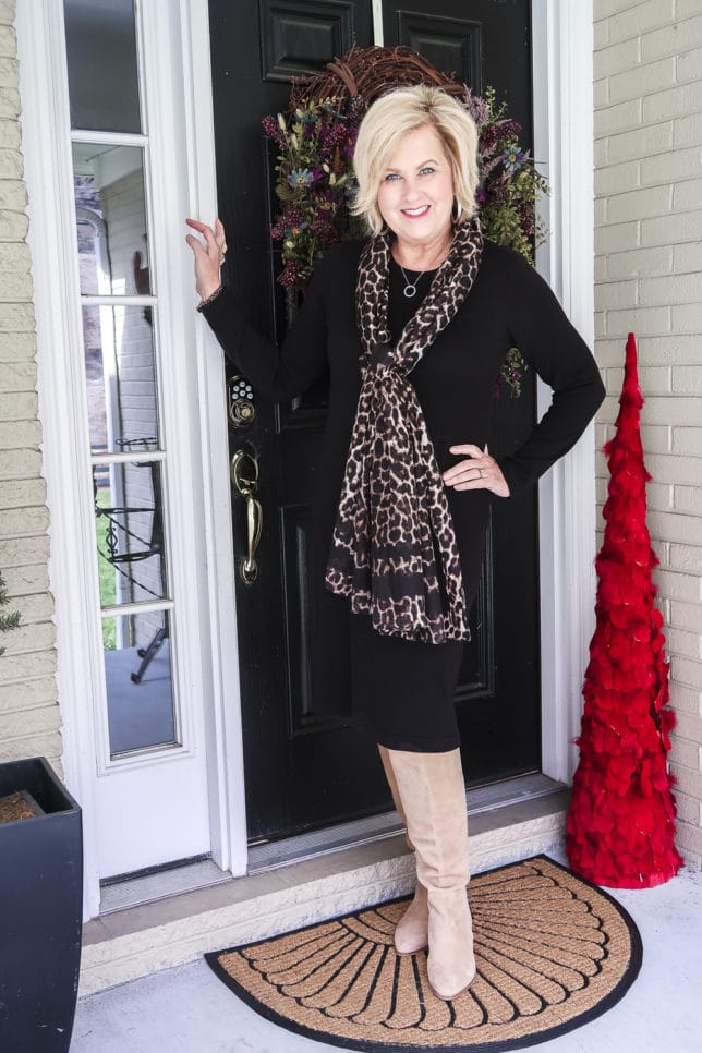 Fashion blogger 50 Is Not Old shows us how a classic black sweater dress looks updated with the addition of the leopard print scarf and suede knee boots.