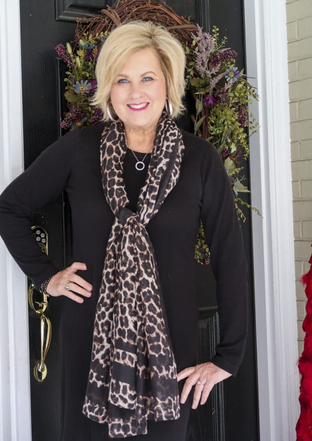 Fashion blogger 50 Is Not Old shows us how a classic black sweater dress looks updated with the addition of the leopard print scarf