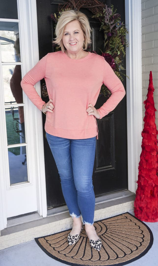 Fashion Blogger 50 Is Not Old is wearing a rose/coral tunic top and a pair of chewed hem jeans and leopard flats