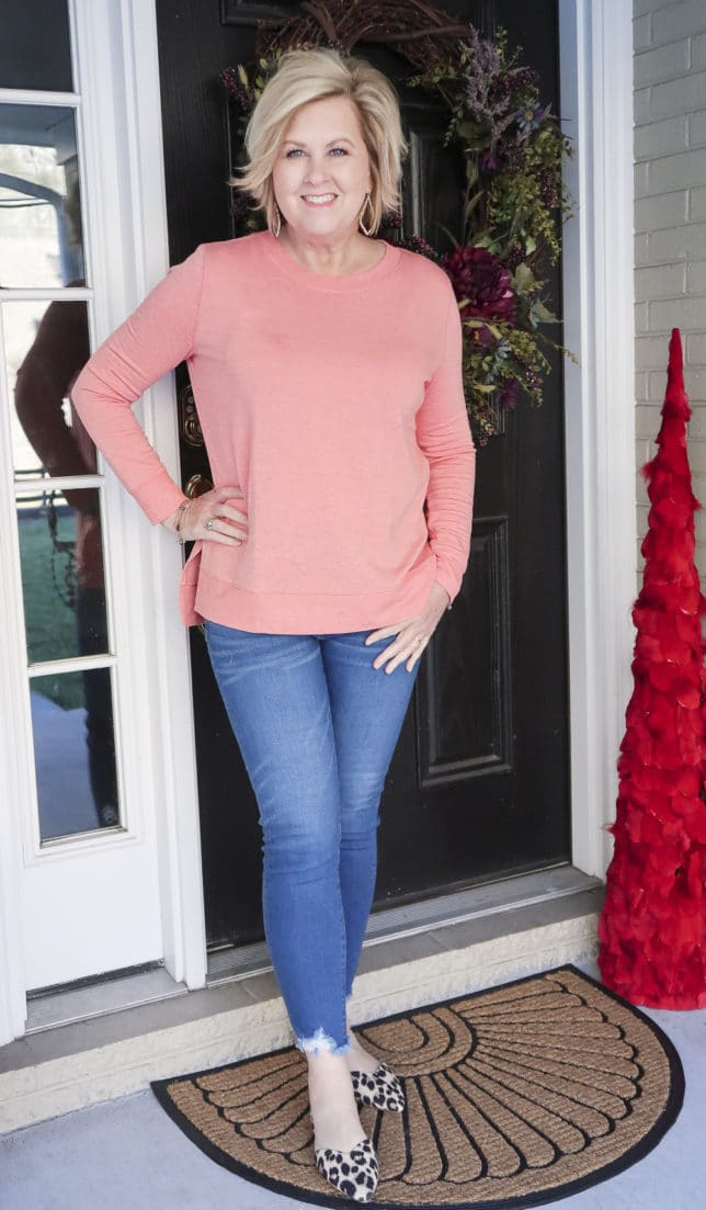 Fashion Blogger 50 Is Not Old is wearing a soft coral tunic top and a pair of chewed hem jeans with leopard flats