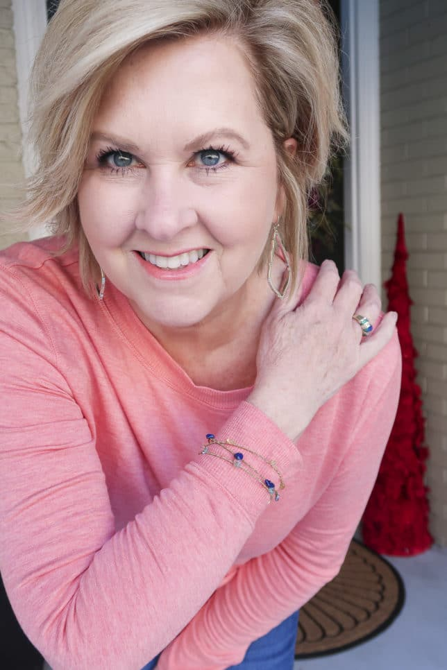 Fashion Blogger 50 Is Not Old is wearing a soft rose/coral tunic top and a pair of gold earrings