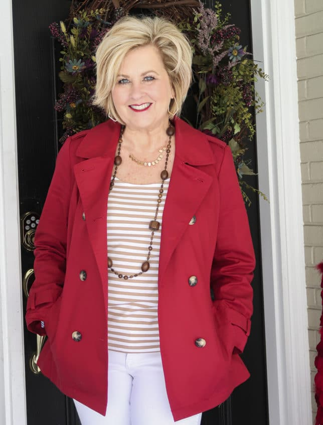 Fashion Blogger 50 Is Not Old is wearing a tan striped top and a red trench coat