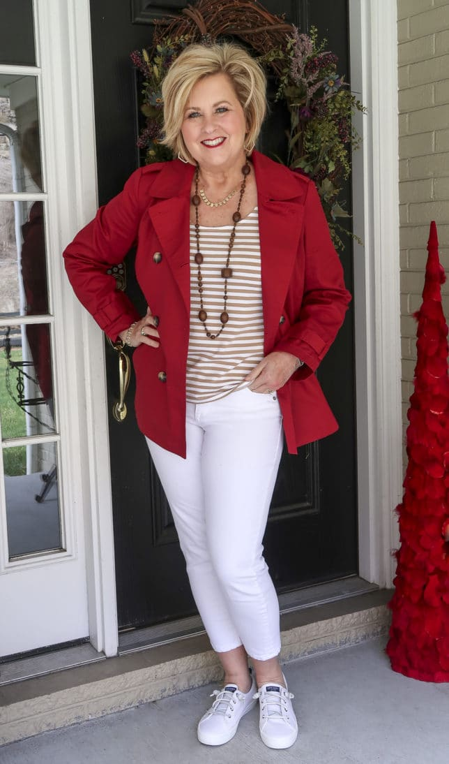 Fashion Blogger 50 Is Not Old is wearing her rainy weather style of a pair of white jeans with a tan striped top and a red trench coat