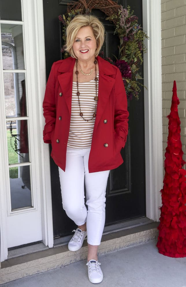 Fashion Blogger 50 Is Not Old is wearing a pair of white jeans with a tan striped top and a red trench coat with Sperry sneakers
