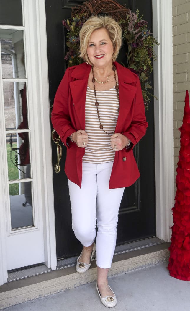 Fashion Blogger 50 Is Not Old is wearing a pair of white jeans with a tan striped top and a cranberry red trench coat