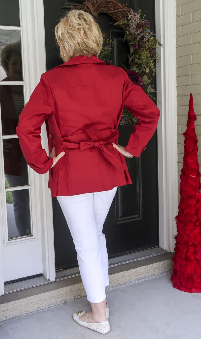 Fashion Blogger 50 Is Not Old is showing the back of a red trench coat
