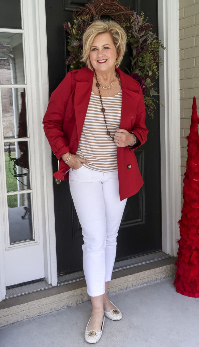 Fashion Blogger 50 Is Not Old is wearing her rainy weather style of a pair of white jeans with a striped top and a red trench coat