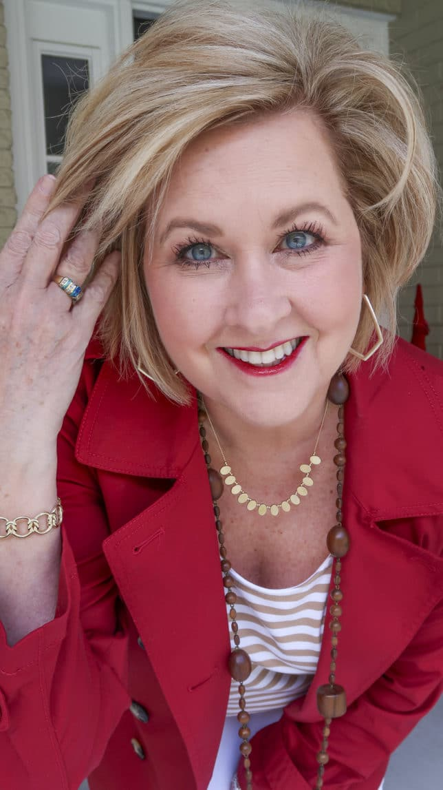 Fashion Blogger 50 Is Not Old is wearing a pair of gold hoop earring from Kendra Scott and a red trench coat