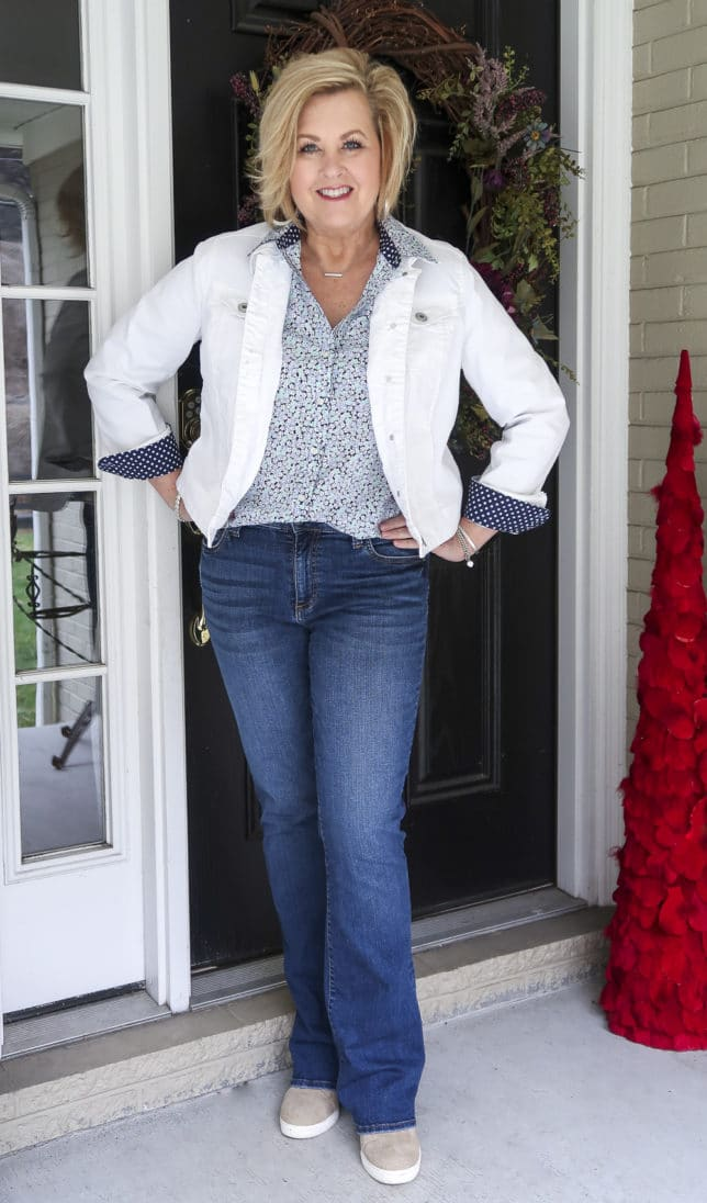 Fashion Blogger 50 Is Not Old wearing a floral shirt, jeans, and a white denim jacket