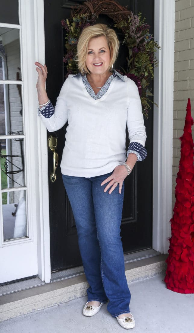 Fashion Blogger 50 Is Not Old wearing a floral shirt, jeans, and a white v-neck sweater