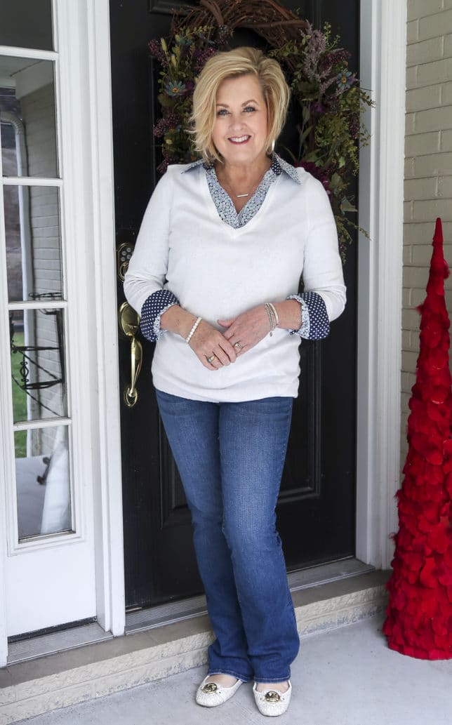 Fashion Blogger 50 Is Not Old wearing a floral shirt and a white v-neck sweater