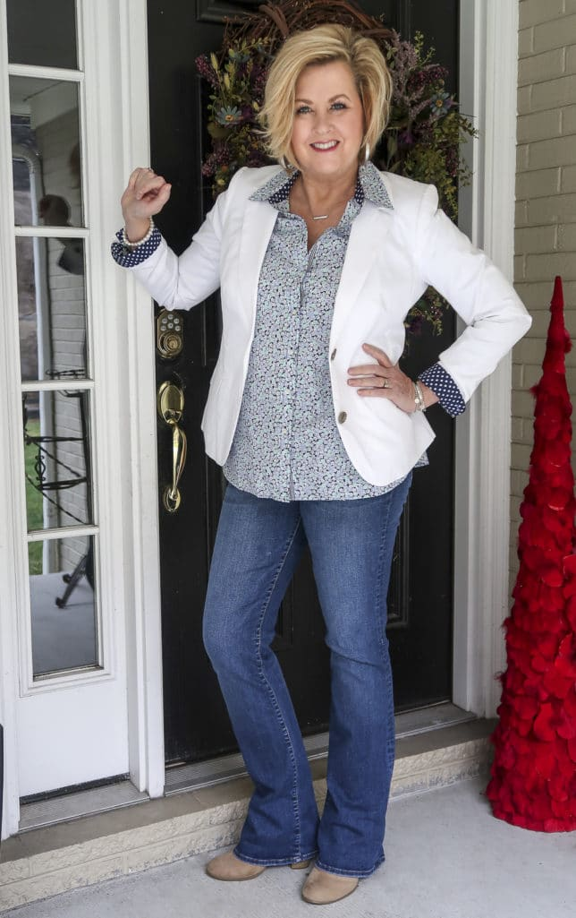 Fashion Blogger 50 Is Not Old wearing a floral shirt, jeans, and a white blazer