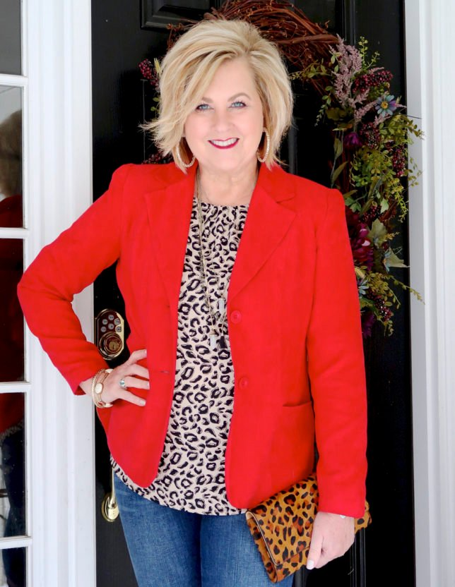 Fashion Blogger 50 Is Not Old is wearing a red blazer, a leopard print top, and carrying a leopard print clutch to a Galentine party