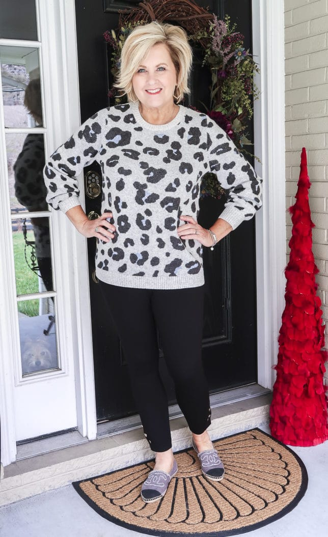 Fashion Blogger 50 Is Not Old wearing a gray leopard print sweater, a pair of black leggings by Chicos, and espadrille shoes by Chanel