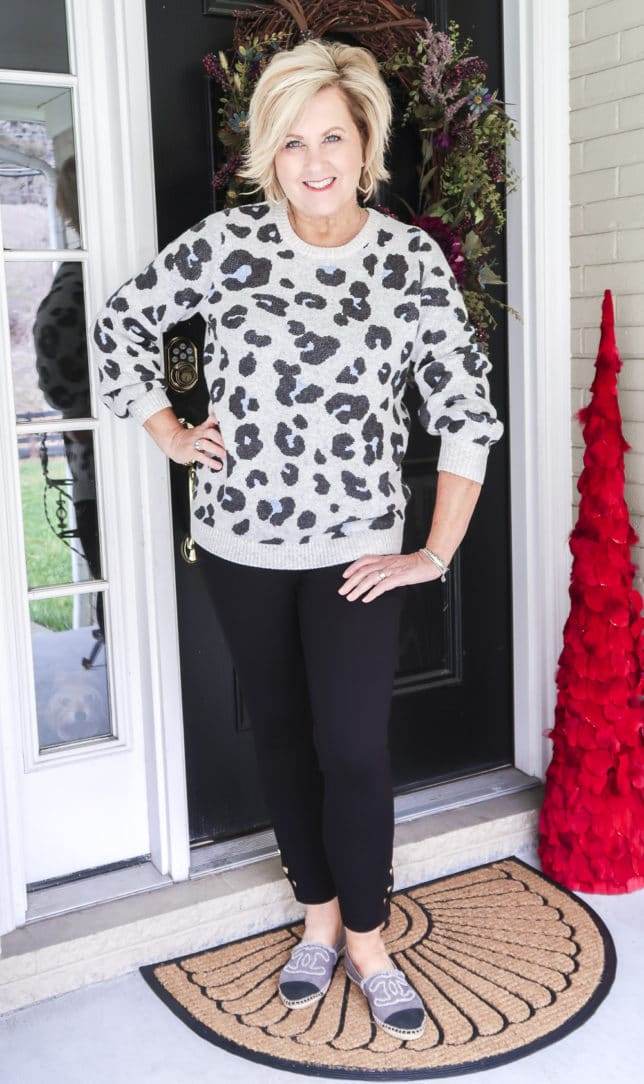 Fashion Blogger 50 Is Not Old wearing a leopard print sweater with a pair of black leggings with snaps on the hem by Chicos