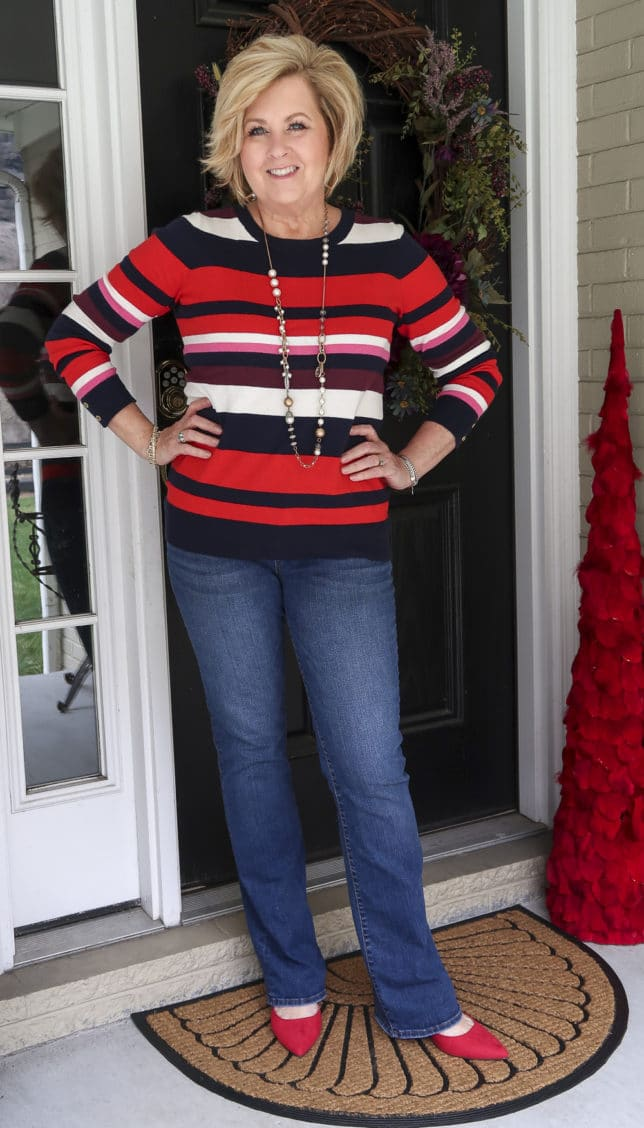 A striped sweater, bootcut jeans, and red shoes are what Fashion Blogger 50 Is Not Old is wearing.