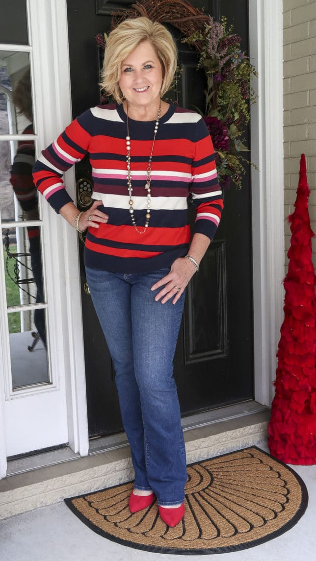 A striped sweater, one of the biggest trends of 2020, jeans, and red shoes are what Fashion Blogger 50 Is Not Old is wearing.