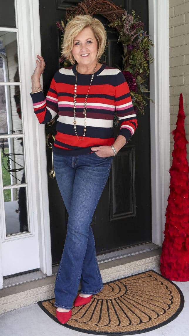 A striped sweater from the Loft Outlet, one of the biggest trends of 2020, jeans, and red shoes are what Fashion Blogger 50 Is Not Old is wearing.