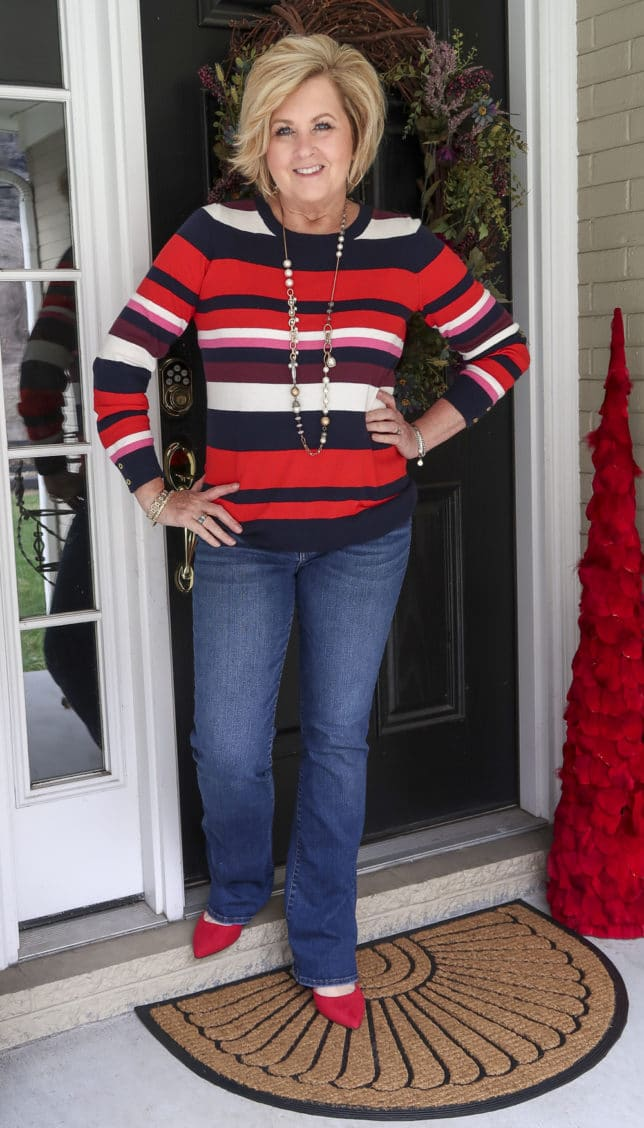 A striped sweater, one of the biggest trends of 2020, bootcut jeans, and red shoes are what Fashion Blogger 50 Is Not Old is wearing.