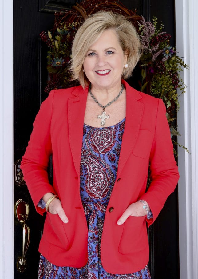 A bright apple red blazer and a paisley dress worn with a cross necklace by Fashion Blogger 50 Is Not Old