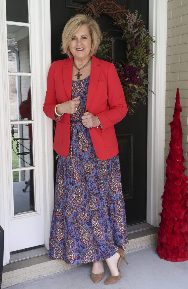 A bright apple red blazer and a spring paisley dress worn by Fashion Blogger 50 Is Not Old