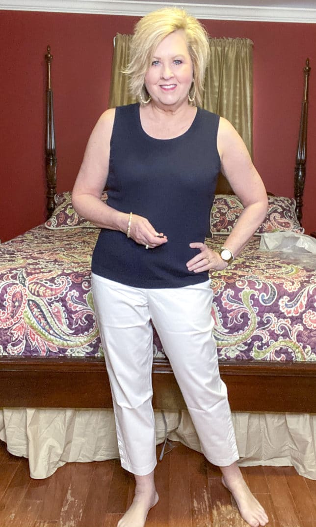 Blogger 50 Is Not Old wearing a navy top and white crop pants