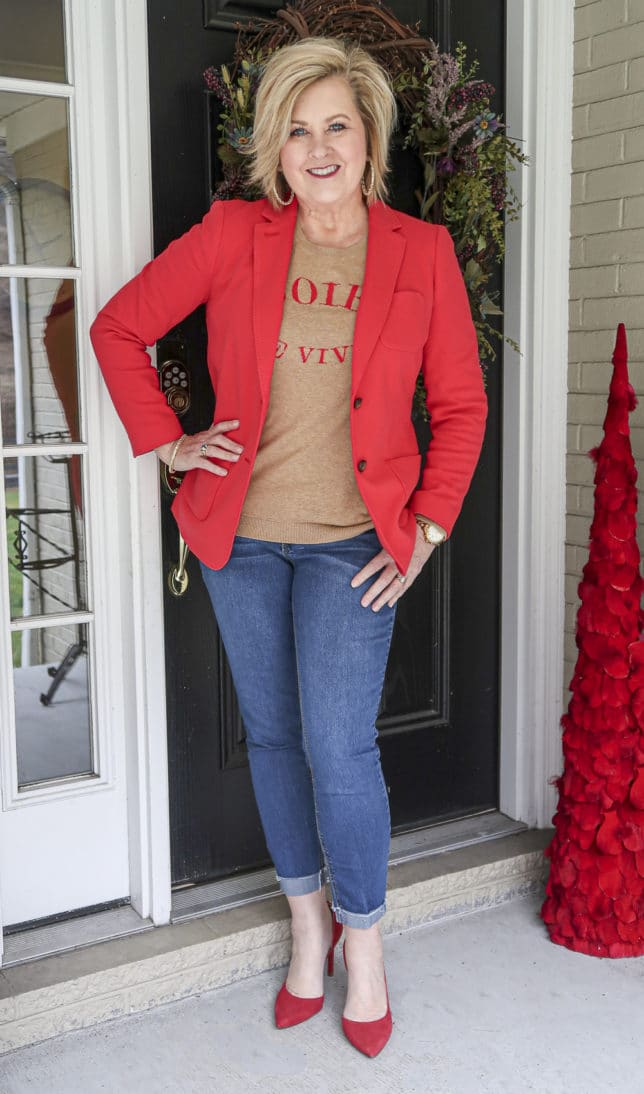 Fashion Blogger 50 Is Not Old wearing a red blazer and a tan sweater with cuffed jeans and red pumps