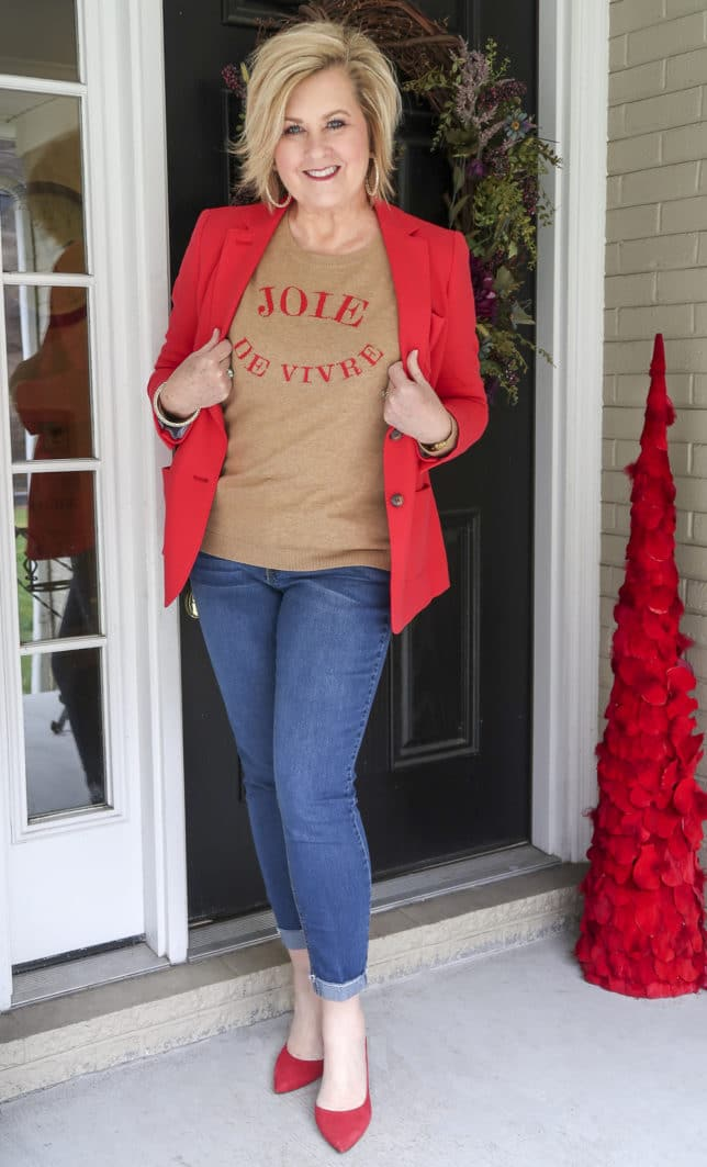 Fashion Blogger 50 Is Not Old wearing a red blazer and a tan sweater with Joie De Vivre written on it and cuffed jeans and red pumps