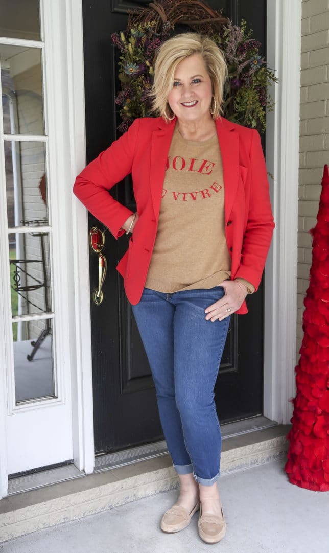 Fashion Blogger 50 Is Not Old wearing a red blazer and a tan sweater with cuffed jeans and suede loafers