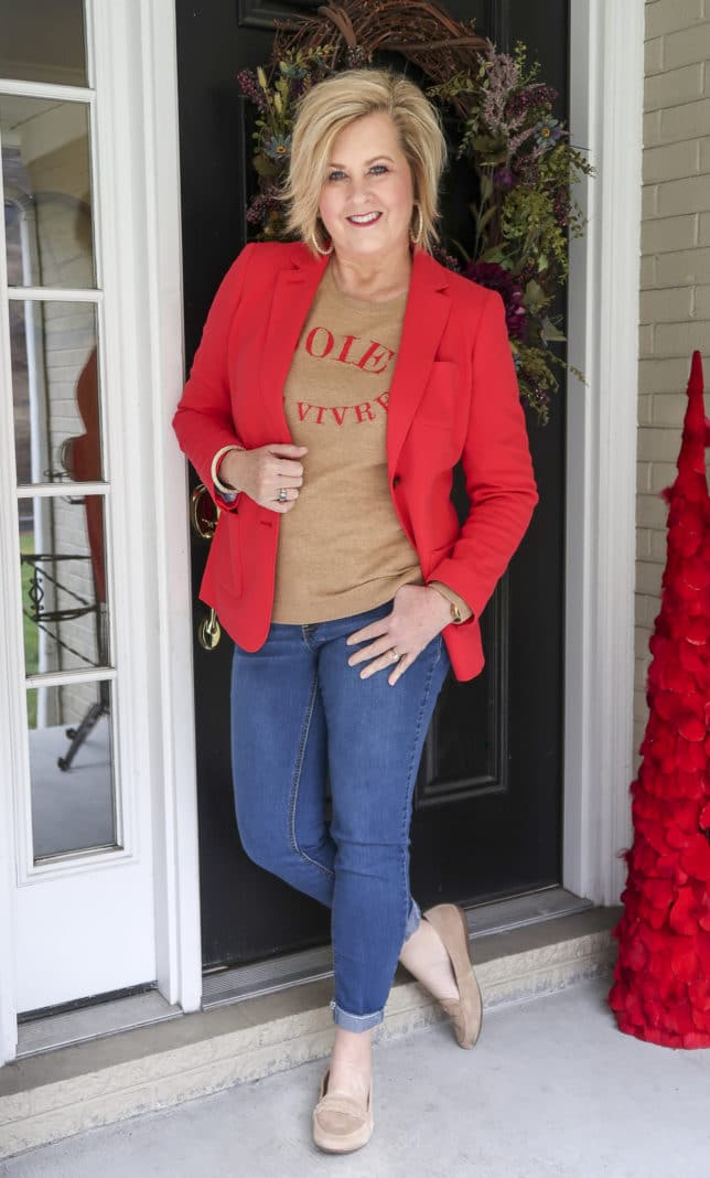 Fashion Blogger 50 Is Not Old wearing a red blazer and a tan sweater with jeans and suede loafers