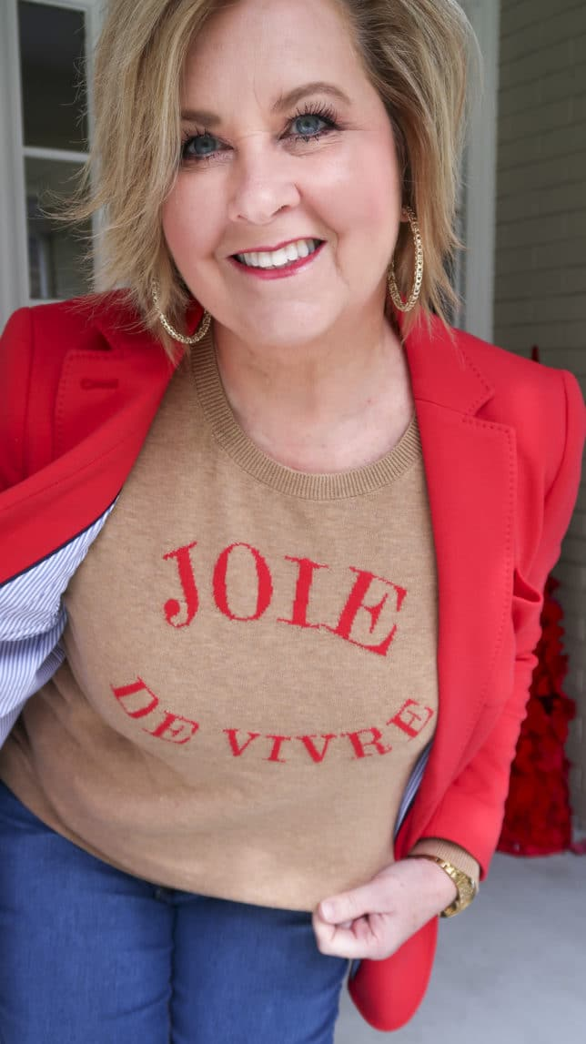 Fashion Blogger 50 Is Not Old wearing a red blazer and a tan sweater with Joie De Vivre which means zest for life