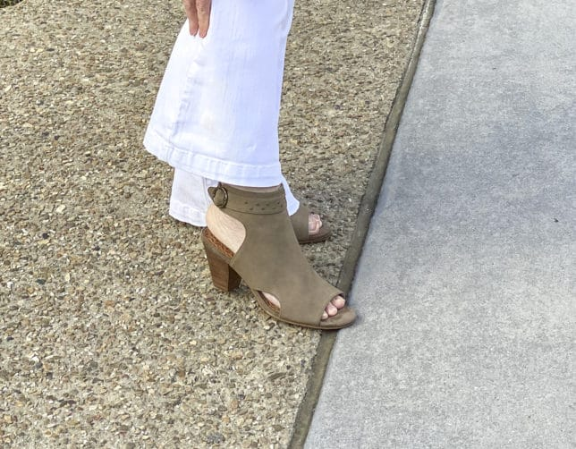 Fashion Blogger 50 Is Not Old is styling white flare jeans by Sofia Vergara, and a pair of ankle boots by Baretraps
