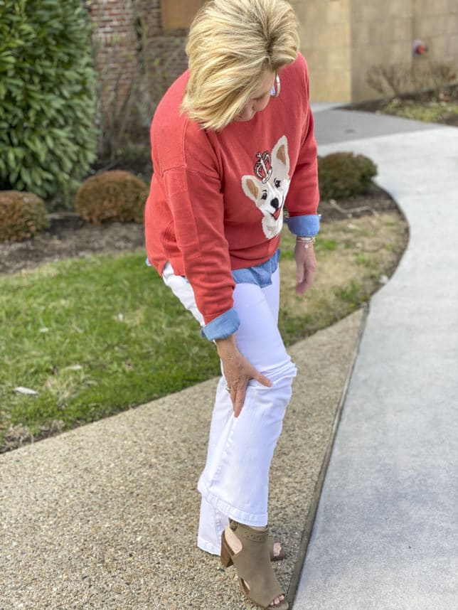 Fashion Blogger 50 Is Not Old is styling a coral sweater that has a Corgi dog on it with white flare jeans by Sofia Vergara, and a pair of ankle boots