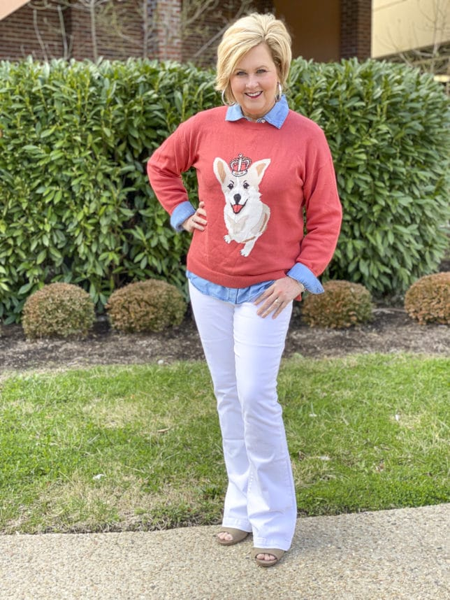 Fashion Blogger 50 Is Not Old is styling a coral sweater that has a Corgi dog on it with white flare jeans and a denim button up