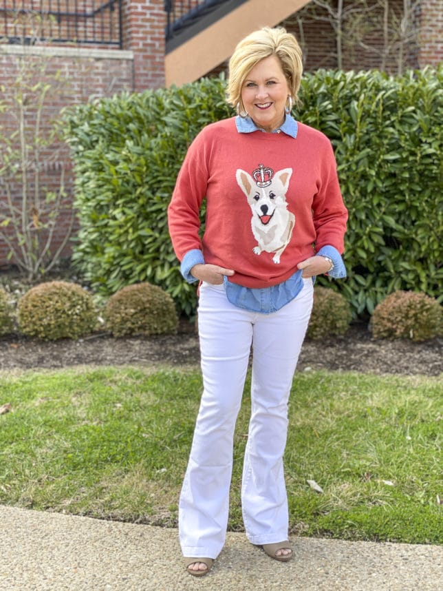 Fashion Blogger 50 Is Not Old is styling a coral sweater that has a Corgi dog on it with white flare jeans by Sofia Vergara, a lightweight denim shirt by EV1, and a denim button up