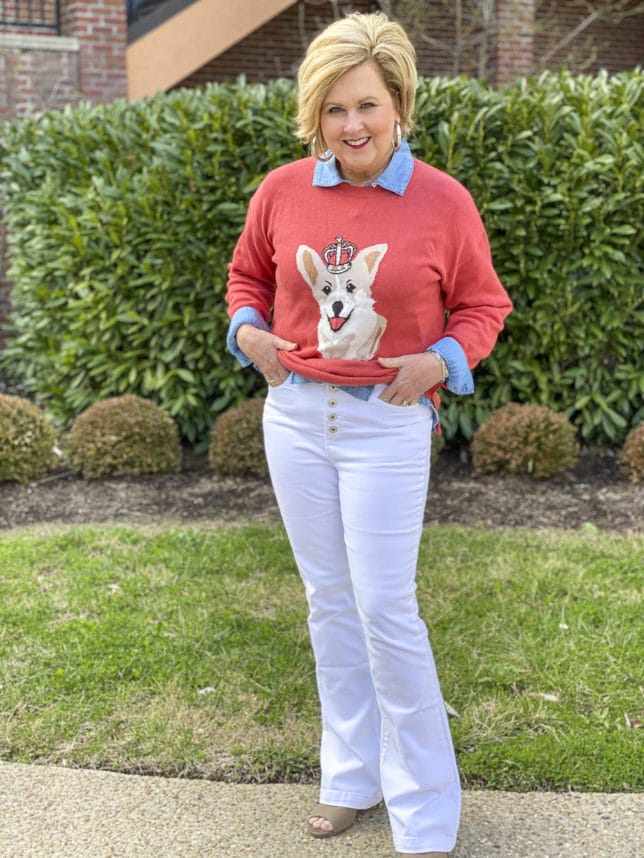 Fashion Blogger 50 Is Not Old is styling a coral sweater that has a Corgi dog on it with white flare jeans by Sofia Vergara, and a denim button up