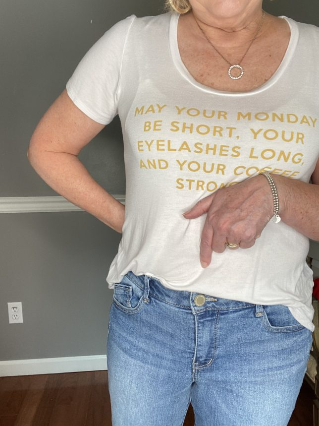 Fashion Blogger 50 Is Not Old in a white t-shirt with gold writing and showing the rise of a pair ofjeans