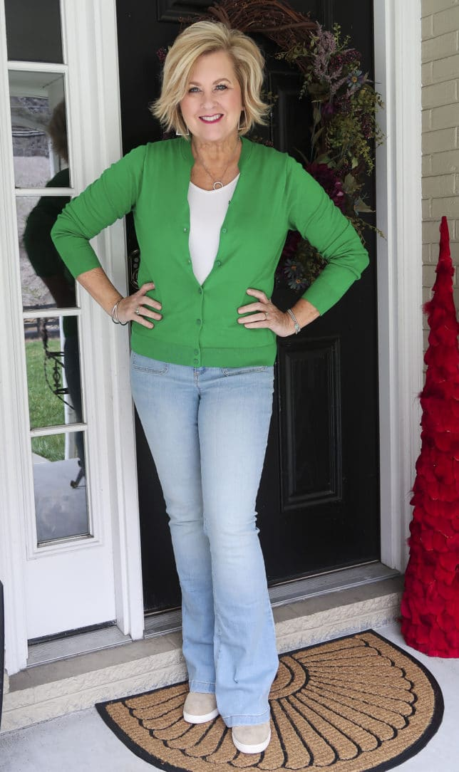Fashion Blogger 50 Is Not Old wearing a bright green cardigan with faded flared jeans