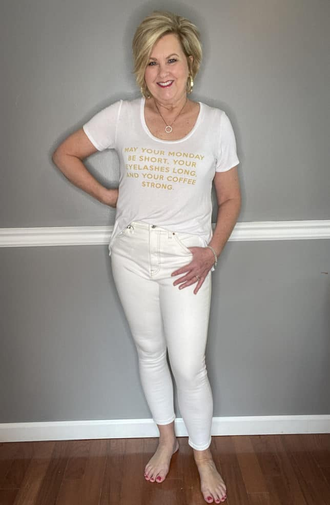 Fashion Blogger 50 Is Not Old in a white t-shirt with gold writing and cream colored jeans