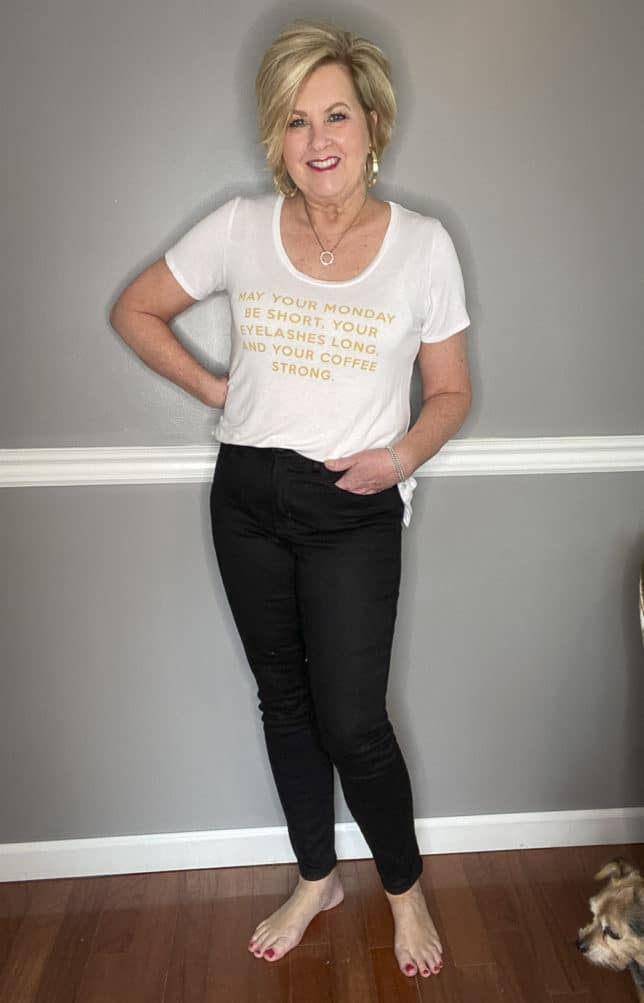 Fashion Blogger 50 Is Not Old in a white t-shirt with gold writing and black jeans