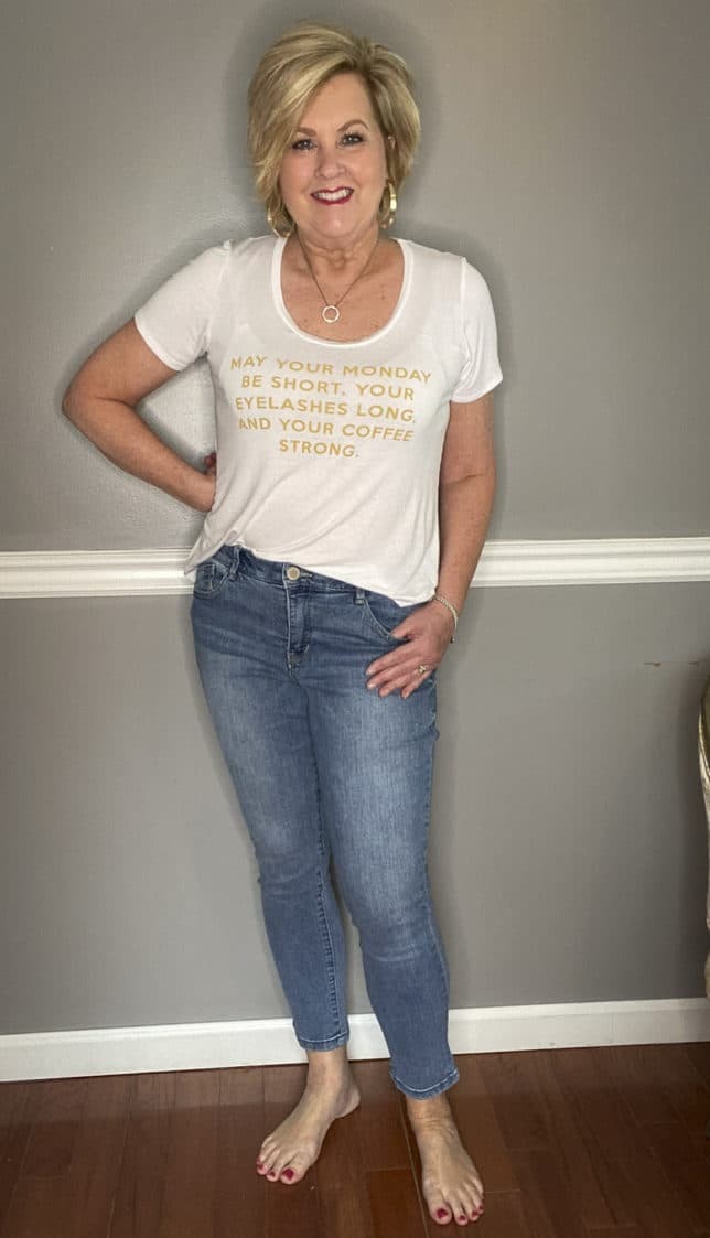 Fashion Blogger 50 Is Not Old in a white t-shirt with gold writing and ankle jeans