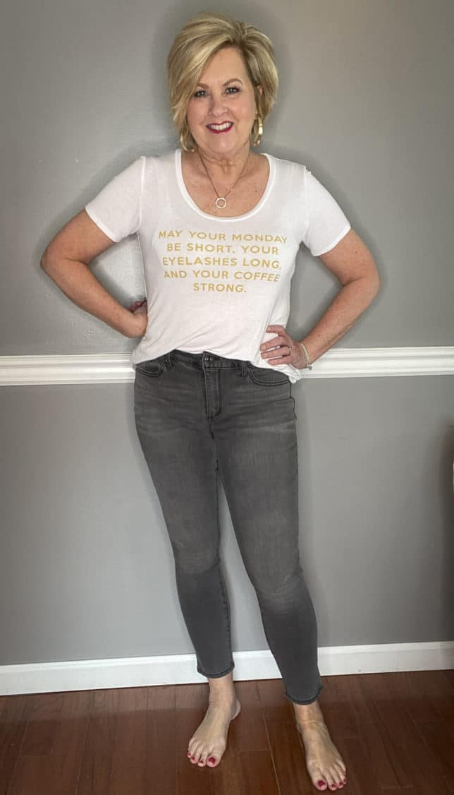 Fashion Blogger 50 Is Not Old in a white t-shirt with gold writing and gray jeans