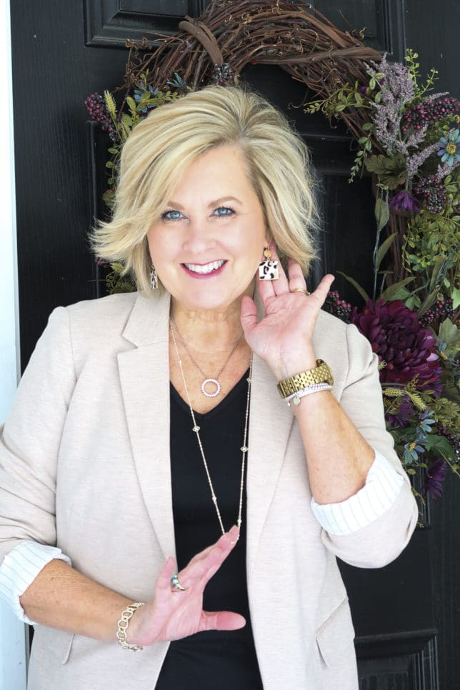 Fashion Blogger 50 Is Not Old in a taupe Ponte knit blazer, a black v-neck t-shirt, and leopard print earrings.
