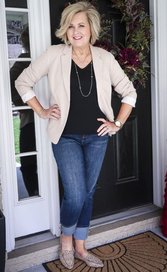 Fashion Blogger 50 Is Not Old in a taupe knit blazer, a black v-neck t-shirt, and cuffed jeans